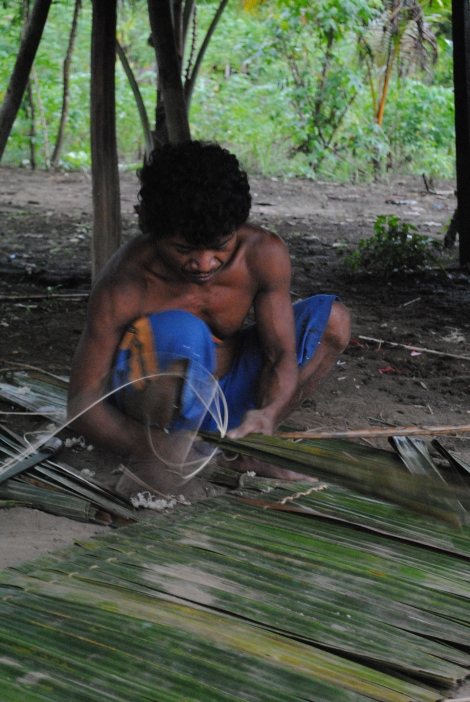 A Villager Weaves Together Pandanus Leaves for his Roof
