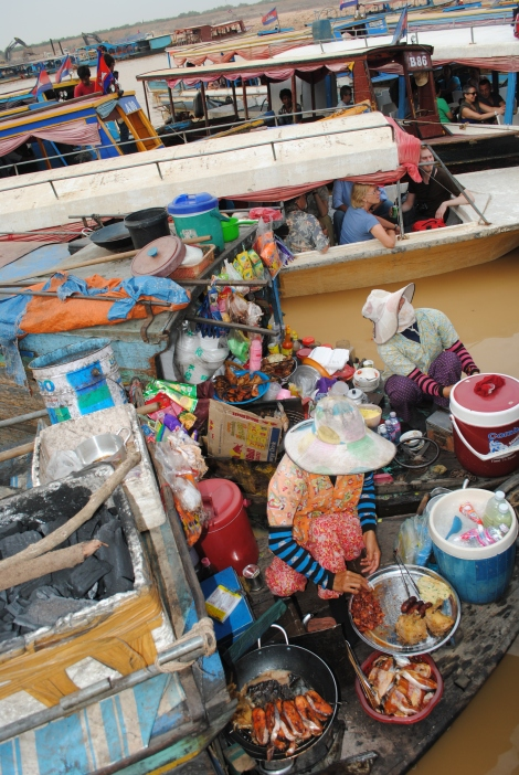 Women cook food and sell goods from small boats at the ferry dock.