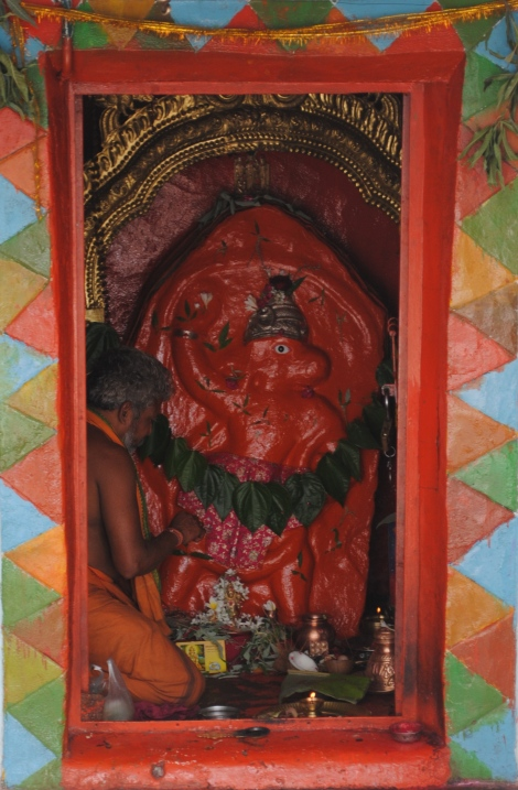 A sadhu prays at a shrine to the monkey god, Hanuman